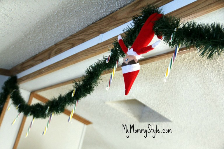 elf on the shelf hanging on the garland with candy canes