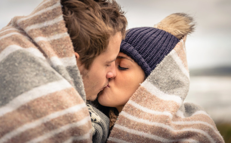 Young couple kissing outdoors under blanket in a cold day