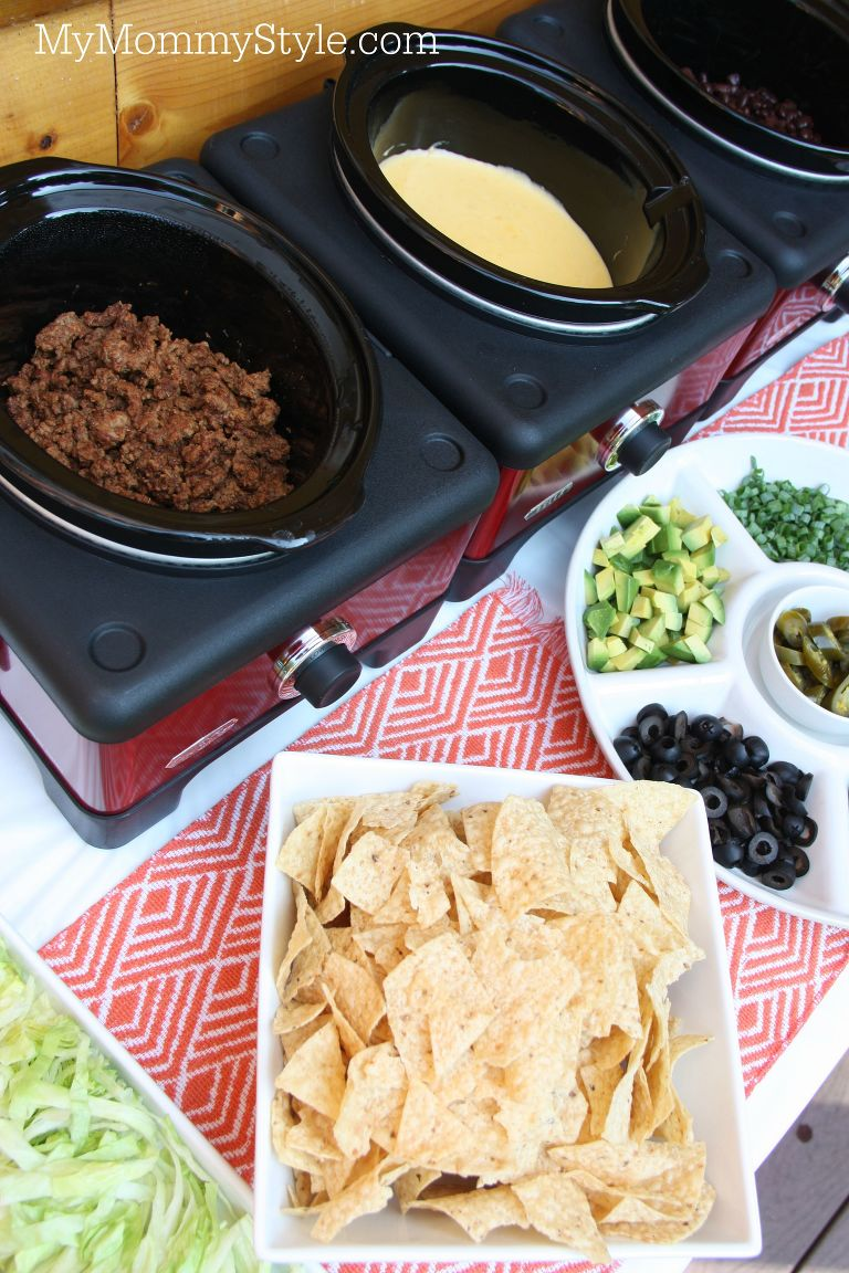 Nacho bar with slow cookers, chips cheese, meat and nacho toppings.