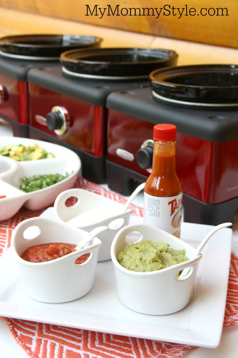 Plate of nacho bar condiments including salsa, sour cream, guacamole, and hot sauce.