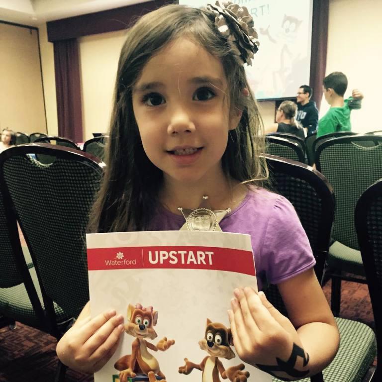 Child holding Upstart Utah packet