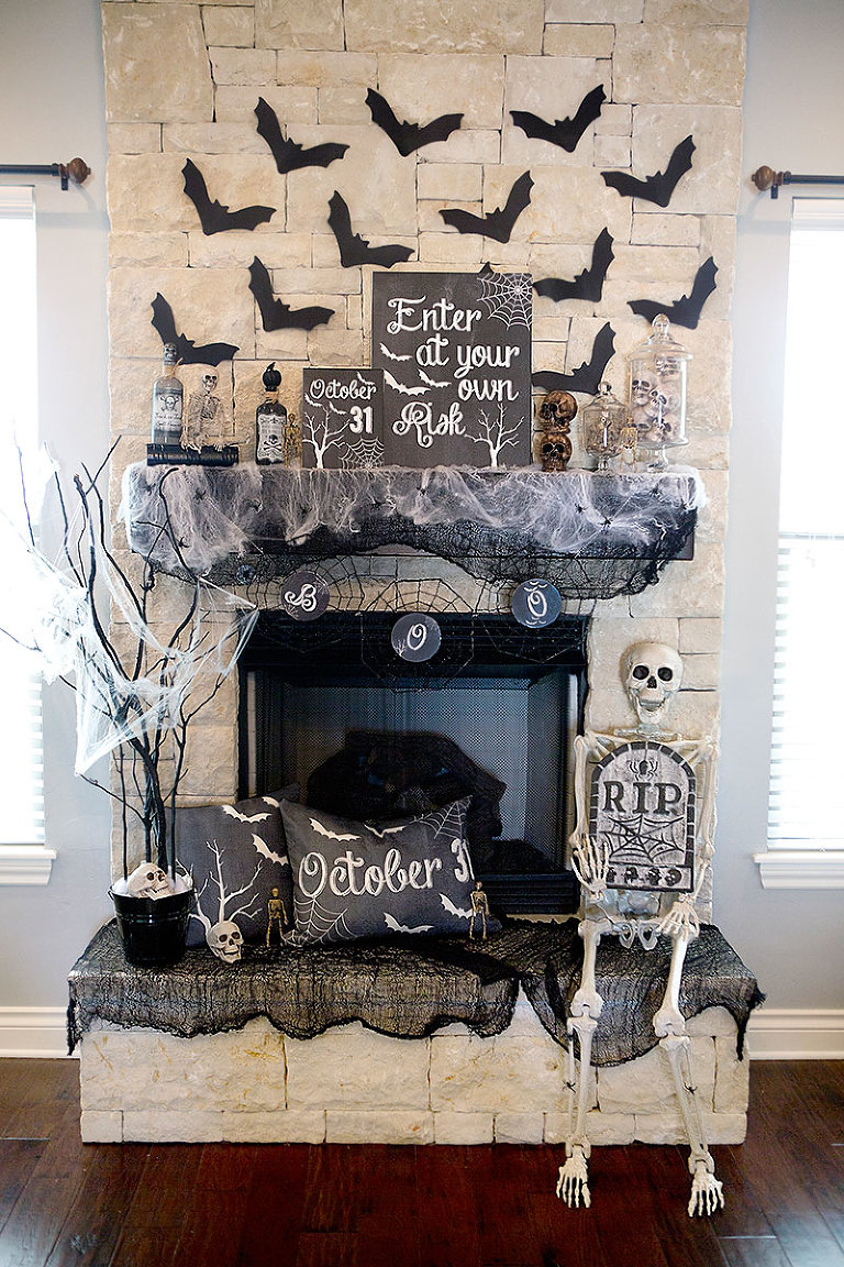 Halloween mantel with bats flying up the stone wall.