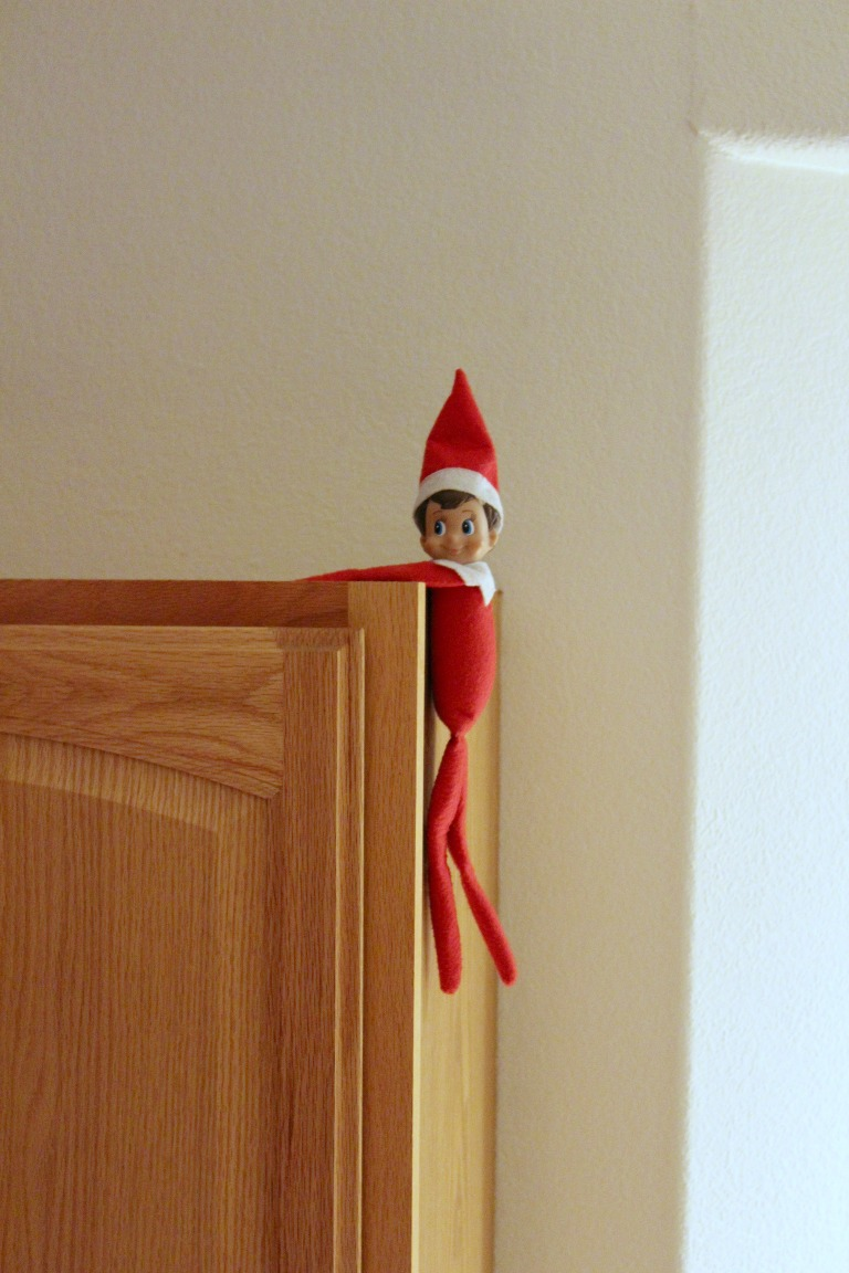 Elf on the Shelf hanging onto the cupboard
