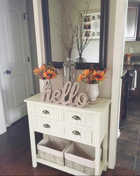 Small white entrance table with flowers on top.