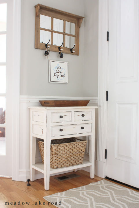 Small white entrance table with key hooks above.