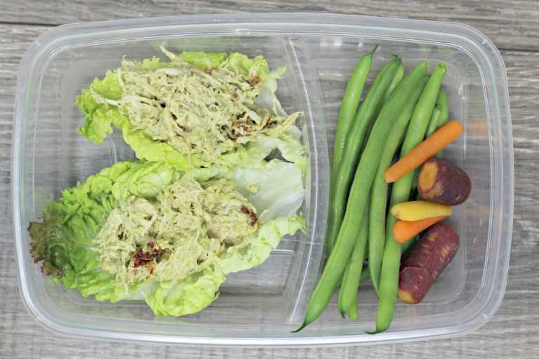 Low calorie meal prep bowl with pesto chicken salad on top of romaine lettuce spears with a side of green beens and multi-colored carrots.