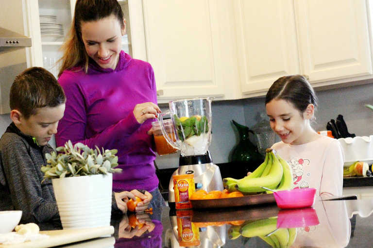 Mom with kids making a smoothie for the Metamucil challenge.