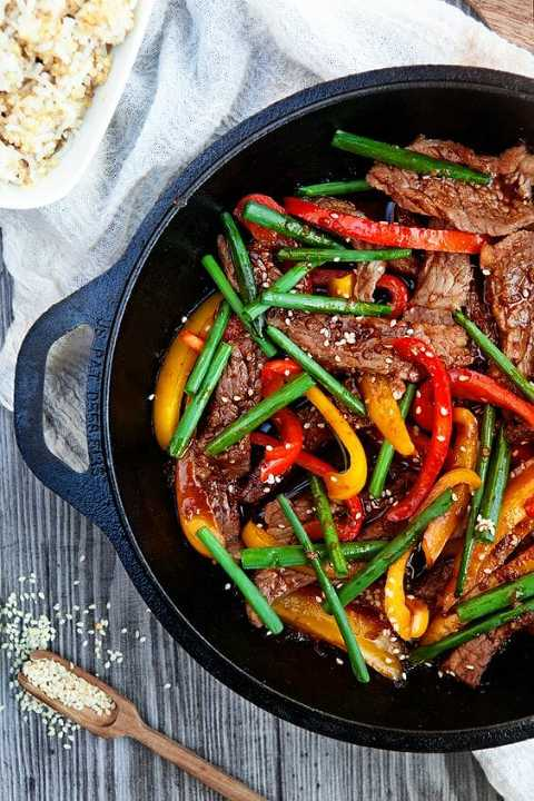 Beef stir fry with red and yellow peppers and green onions in a large skillet.