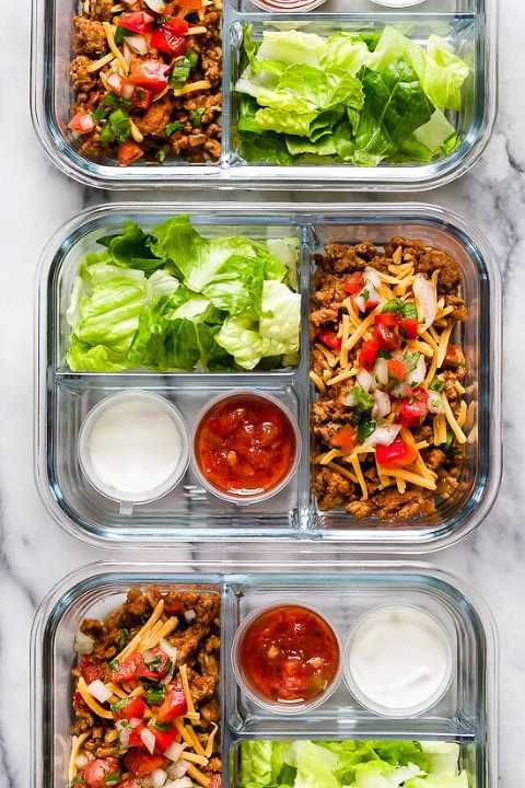 Deconstructed Taco Salad  in a meal prep dish with lettuce, ground turkey, cheese, pico, salsa and sour cream.