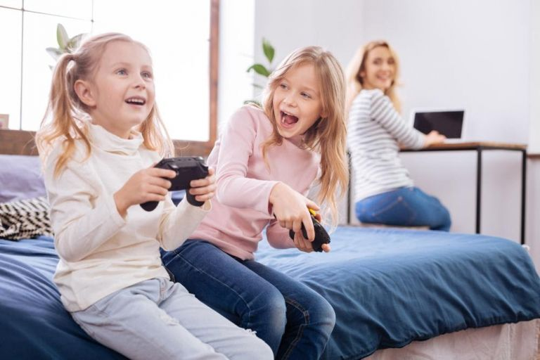 kids playing video games while mom working from home