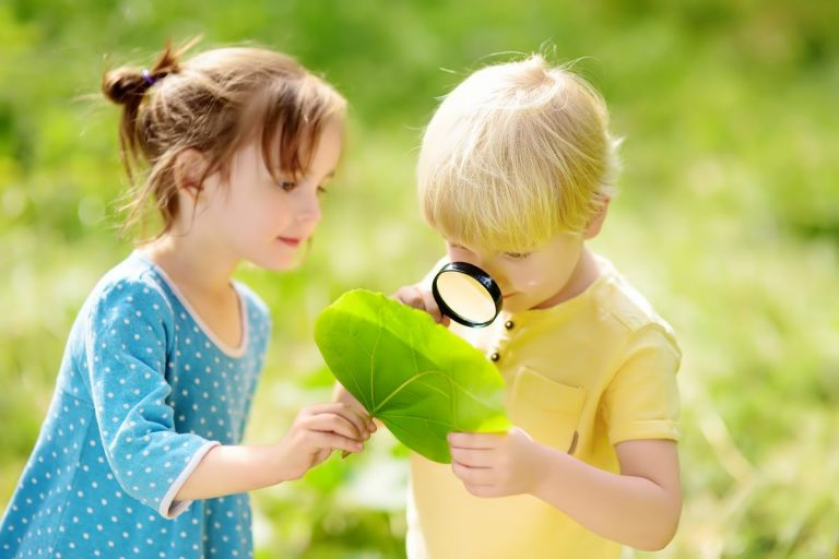 Boy and Girl looking at a leaf under magnifying glass